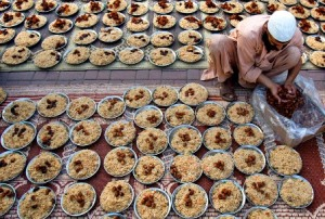 A man arranges plates with meals for Iftar (AP Photo/Anjum Naveed)